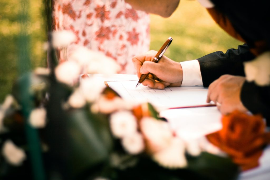 Groom signing antenuptial contracts